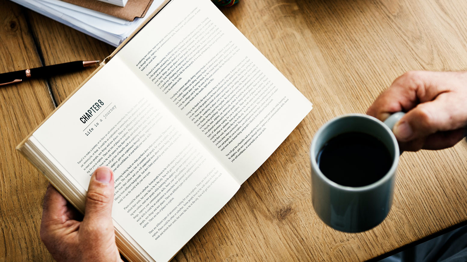 Person reading a book while drinking coffee
