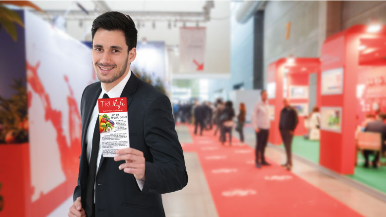 Booth presenter handing a brochure