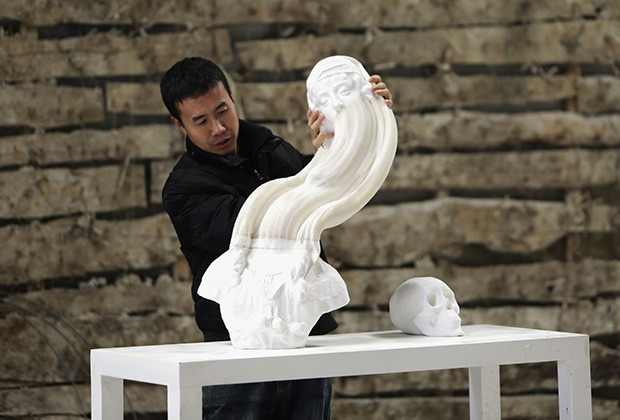 Chinese artist Li Hongbo stretches a paper sculpture work on the outskirts of Beijing