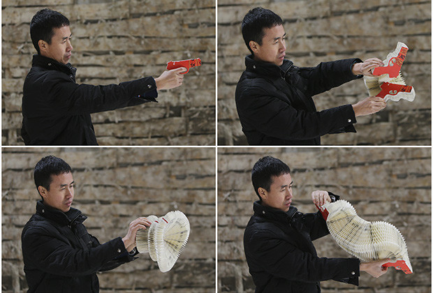 A combination picture shows Chinese artist Li Hongbo playing a paper sculpture of gun on outskirts of Beijing